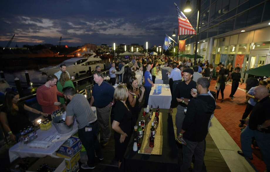 Attendees enjoy samples of food, wine, beer and whiskeys during the Stamford Brew and Whiskey festival along the waterfront at Harbor Point on Thursday in Stamford. Photo: Matthew Brown / Hearst Connecticut Media / Stamford Advocate