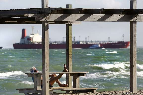 A man rest with his feet propped up at a picnic table on North Beach in Corpus Christi, Monday, Oct. 28, 2013, as a full tanker ship makes its' way to the shipping channel of Port Corpus Christi where the Eagle Ford Consortium is running Oct. 28 through Oct. 30.