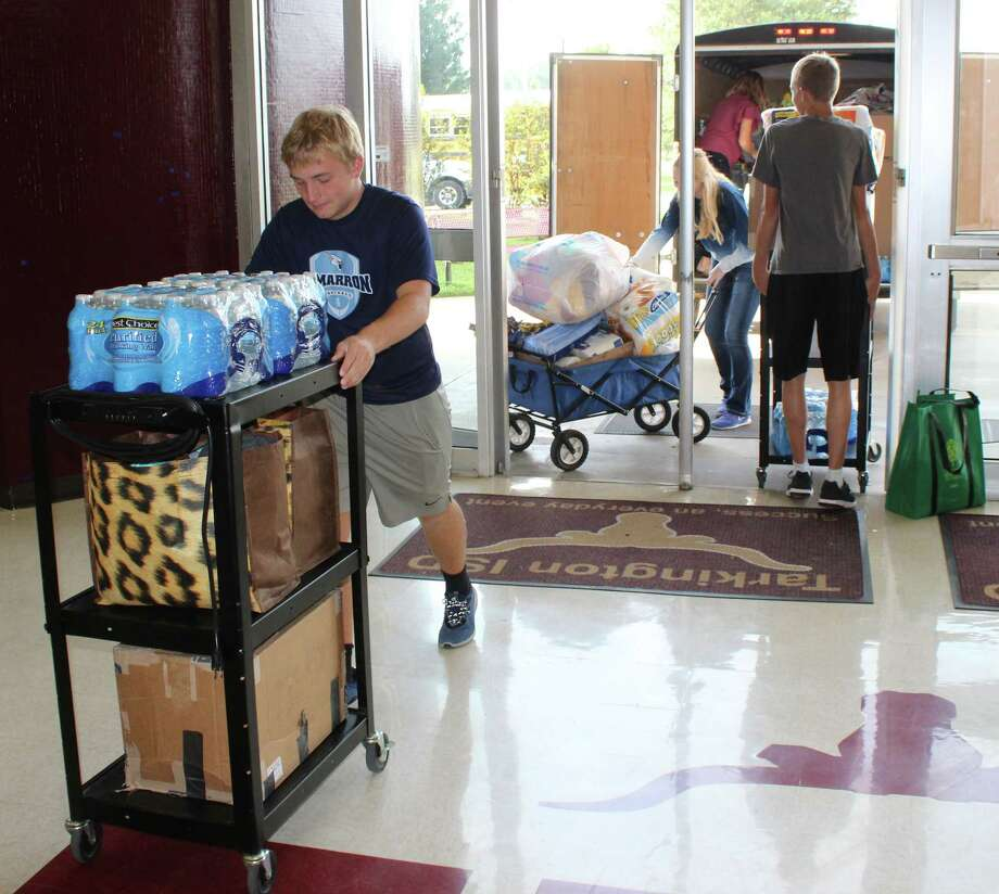 Students of the Kansas Association for Youth at Cimarron High School unload donated supplies for Tarkington Middle School. The donations include pre-packaged food, cleaning supplies, paper towels, shoes, paper good items and more. Photo: Jacob McAdams