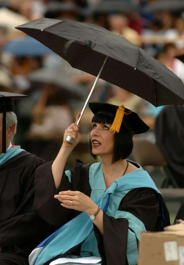 B House Principal, Dr. Linda Paslov, opens her umbrella after it starts to rain, during Trumbull High School's Commencement Exercises in Trumbull, Conn. on Tuesday June 22, 2010. Photo: Christian Abraham / Connecticut Post