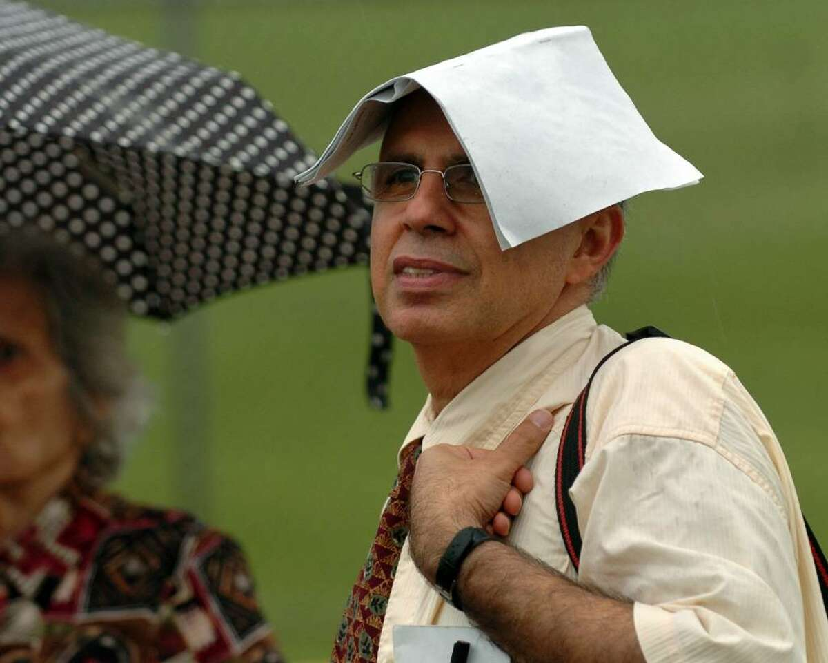 Shahrokh Etemad wears a program to keep the rain off his head as he watches for his son Shervin Eteman, a graduate in Trumbull High School's Commencement Exercises in Trumbull, Conn. on Tuesday June 22, 2010.