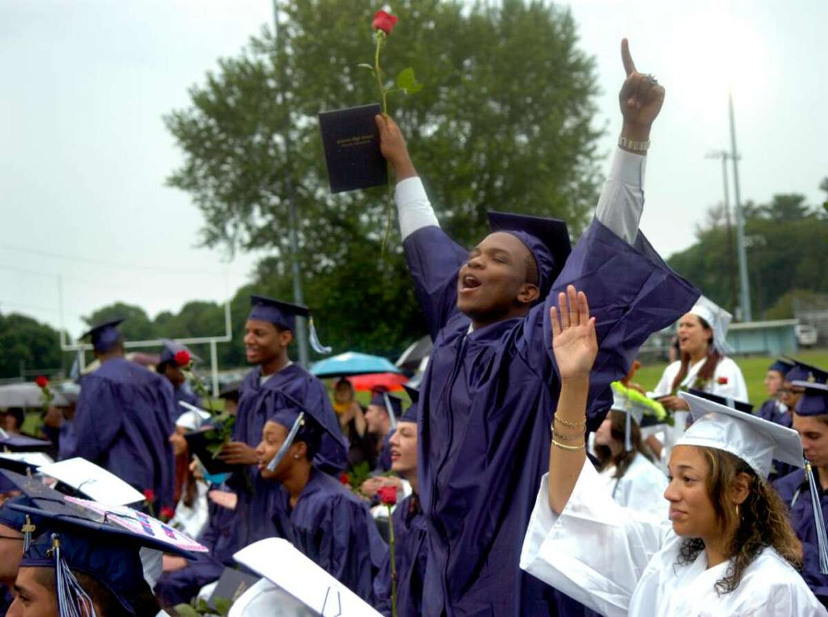 Othniel Jean cheers for classmates as they are awarded their diplomas during the Ansonia High School graduation ceremony Tuesday, June 22, 2010 at Jarvis Field.