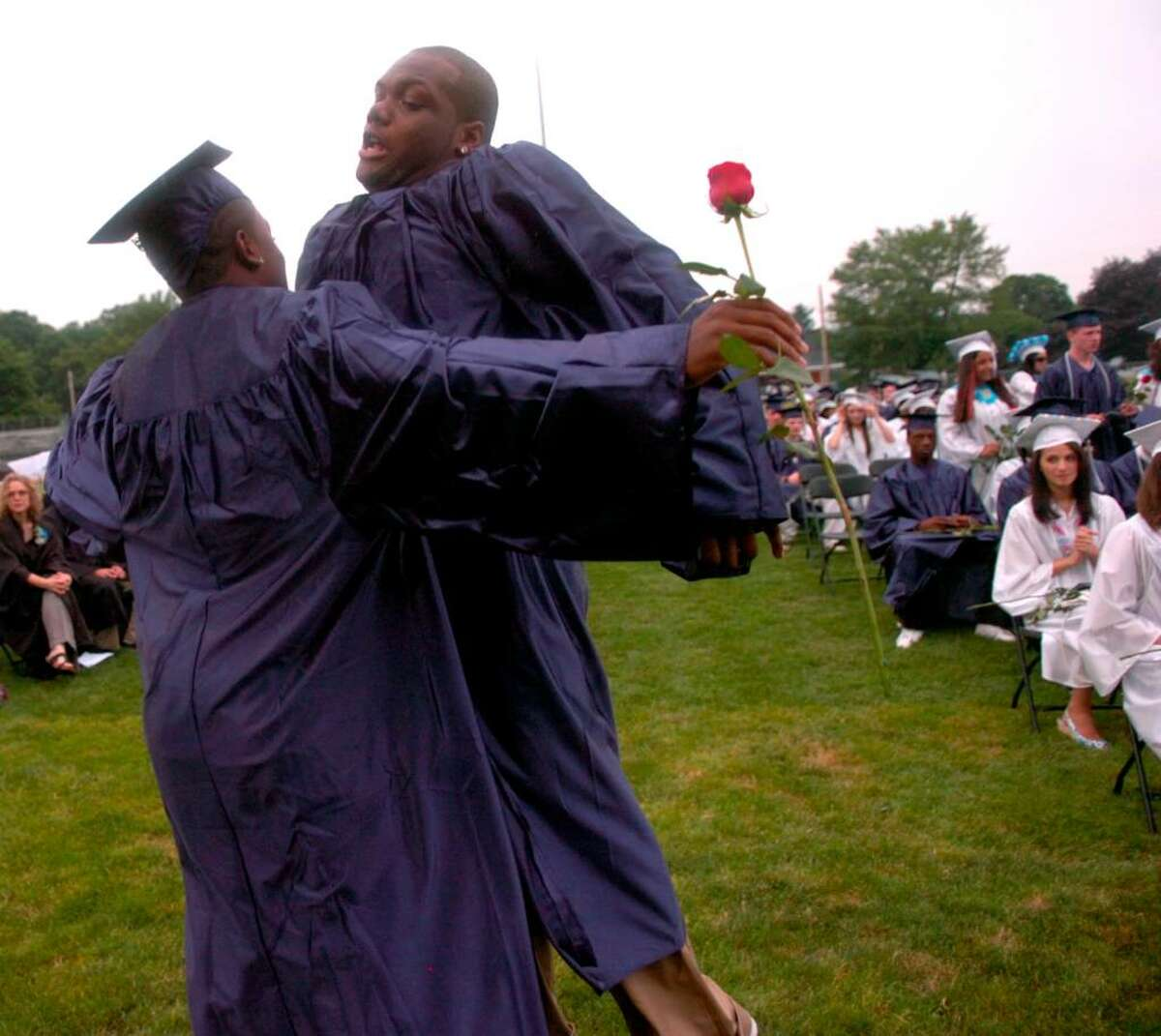 Raymond Beall, right, and Bobby Kinnebrew IV, left, chest bump in celebration of being awarded their diplomas during the Ansonia High School graduation ceremony Tuesday, June 22, 2010 at Jarvis Field.