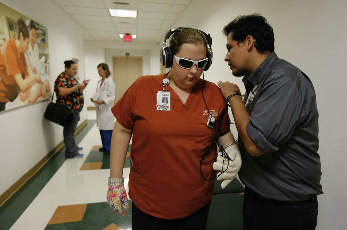 UT School of Nursing's Braulio Amezaga (right) gives instructions to sophomore nursing student Rissa Dunaway before she enters a room while wearing obscured glasses and a headset blaring white noise as part of a
