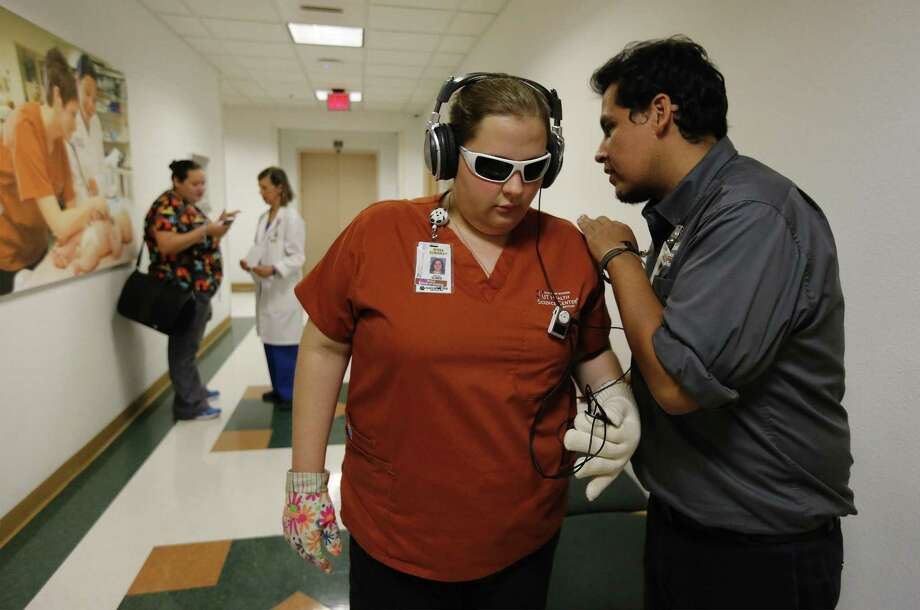 """UT School of Nursing's Braulio Amezaga (right) gives instructions to sophomore nursing student Rissa Dunaway before she enters a room while wearing obscured glasses and a headset blaring white noise as part of a """"virtual dementia tour"""" on Sept. 14, 2017. UT Health San Antonio offered doctors, nurses and students an opportunity to experience what it's like to have dementia. They wore special shoe inserts, glasses and other gadgets. The goal is to raise awareness of the challenges for dementia patients and their caregivers. Photo: Kin Man Hui /San Antonio Express-News / ©2017 San Antonio Express-News"""