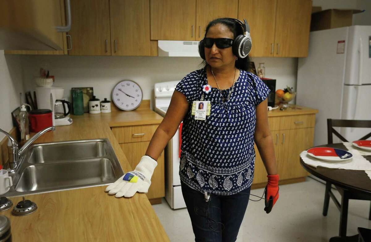 Faculty member Jolly Punchamannil from the School of Nursing at UT Health San Antonio roams in a room attempting to do tasks while outfitted with glasses, gloves and headphones to simulate dementia on Sept. 14, 2017.