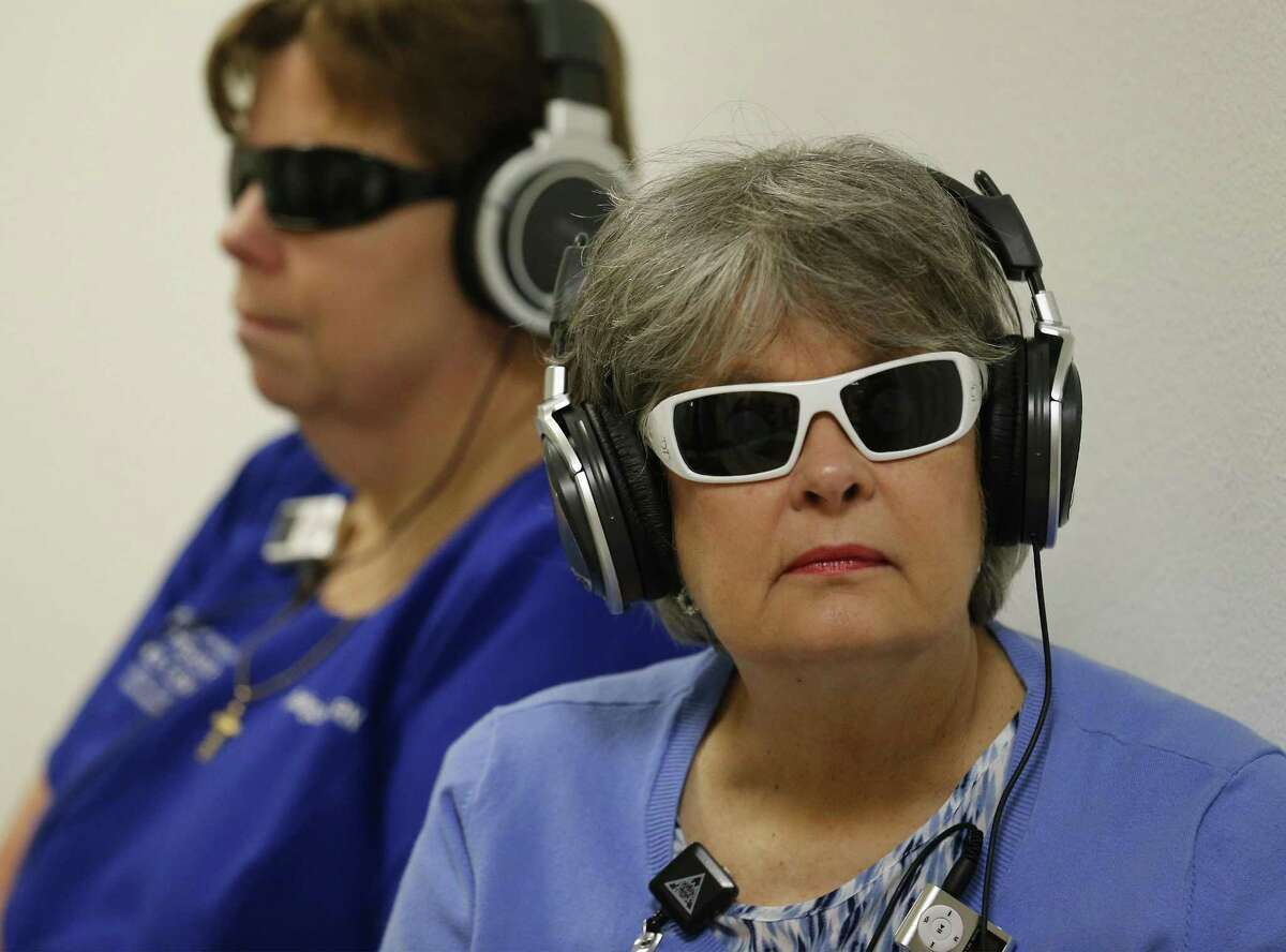 Faculty member Janet Rice (right) and Nancy Rodriguez don glasses and headphones during a