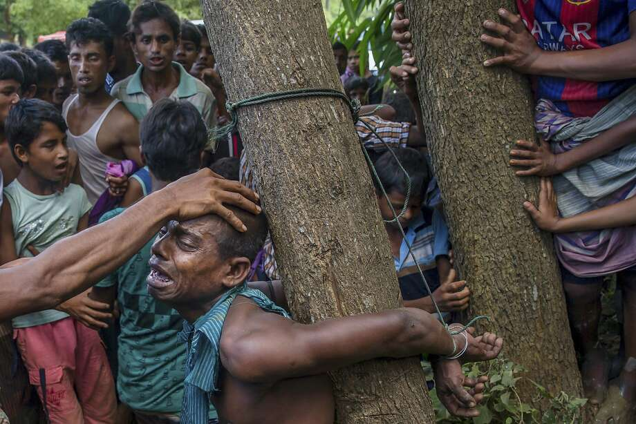 Rohingya Muslims, who recently crossed over from Myanmar into Bangladesh, interrogate a suspected child lifter near Balukhali refugee camp, Bangladesh, Friday, Sept. 15, 2017. Thousands of Rohingya are continuing to stream across the border, with U.N. officials and others demanding that Myanmar halt what they describe as a campaign of ethnic cleansing that has driven nearly 400,000 Rohingya to flee in the past three weeks. (AP Photo/Dar Yasin) Photo: Dar Yasin, Associated Press