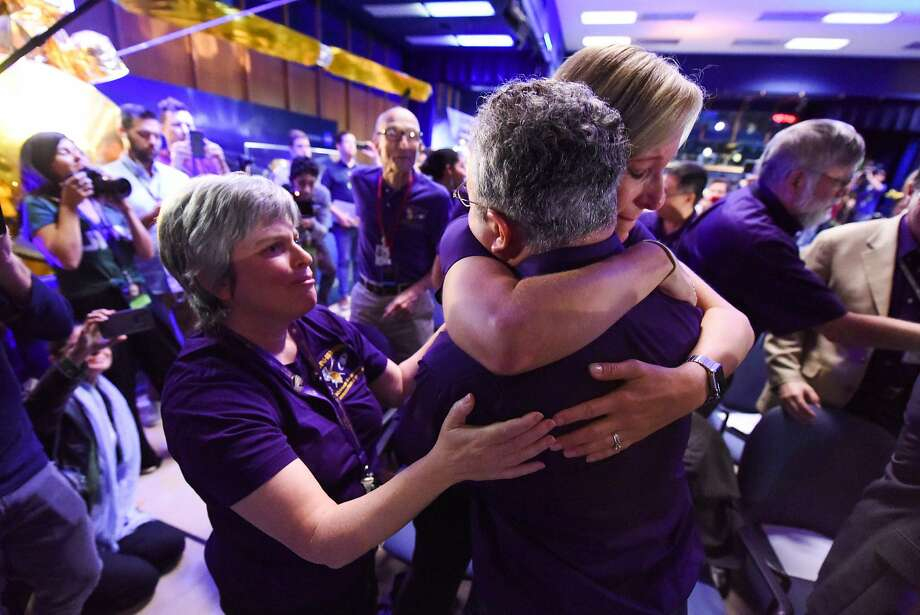 Science team members Jo Pitesky (left), Scott Edgington and Nora Alonge embrace at NASA's Jet Propulsion Laboratory in Pasadena after signals from the spacecraft Cassini ended. Photo: ROBYN BECK, AFP/Getty Images