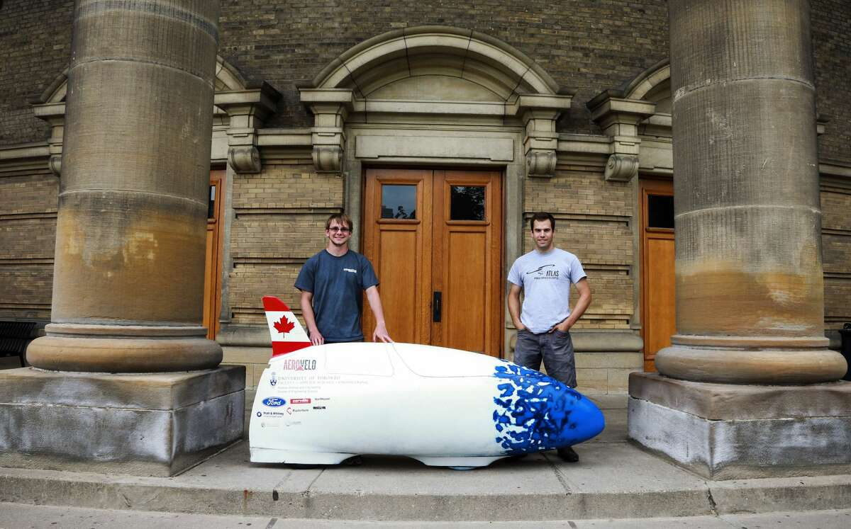 FILE-- Cameron Roberts (R) and Calvin Moes pose by the bike at U of T downtown campus, July 2, 2014. A group of students behind previous projects to build a human-powered ornithopter and helicopter are setting their sights on a new record by building the world's fastest human-powered vehicle. The team's vehicle is expected to hit 140 km/h and will be competing in the World Human-Powered Speed Challenge in Battle Mountain, Nevada this September.