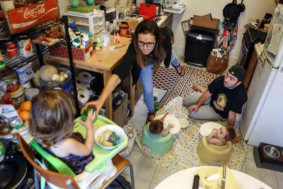 Sarah Montoya and husband Trevor McNeil make due in their cramped kitchen while feeding dinner to their 8 month old twins and two year old daughter on Friday, September 8, 2017 in San Francisco, Calif.