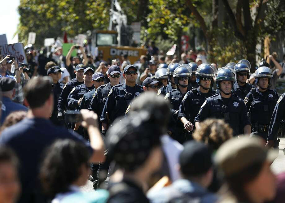 SFPD officers walk in formation through a crowd of protesters towards the park during a protest in response to last-minute Patriot Prayer press conference scheduled to be held at Alamo Square park August 26, 2017 in San Francisco, Calif. Photo: Leah Millis, The Chronicle