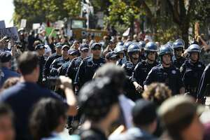 SFPD officers walk in formation through a crowd of protesters towards the park during a protest in response to last-minute Patriot Prayer press conference scheduled to be held at Alamo Square park August 26, 2017 in San Francisco, Calif.