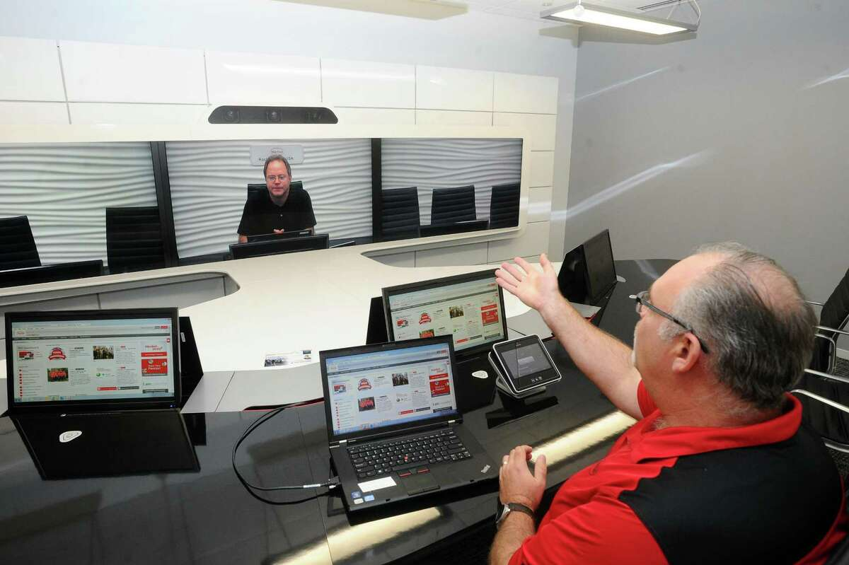 Henkel employee Greg Wolf, right, demonstrates the company's video conference system inside the new offices at 200 Elm St., in downtown Stamford, Conn., on Tuesday, Sept. 12, 2017.