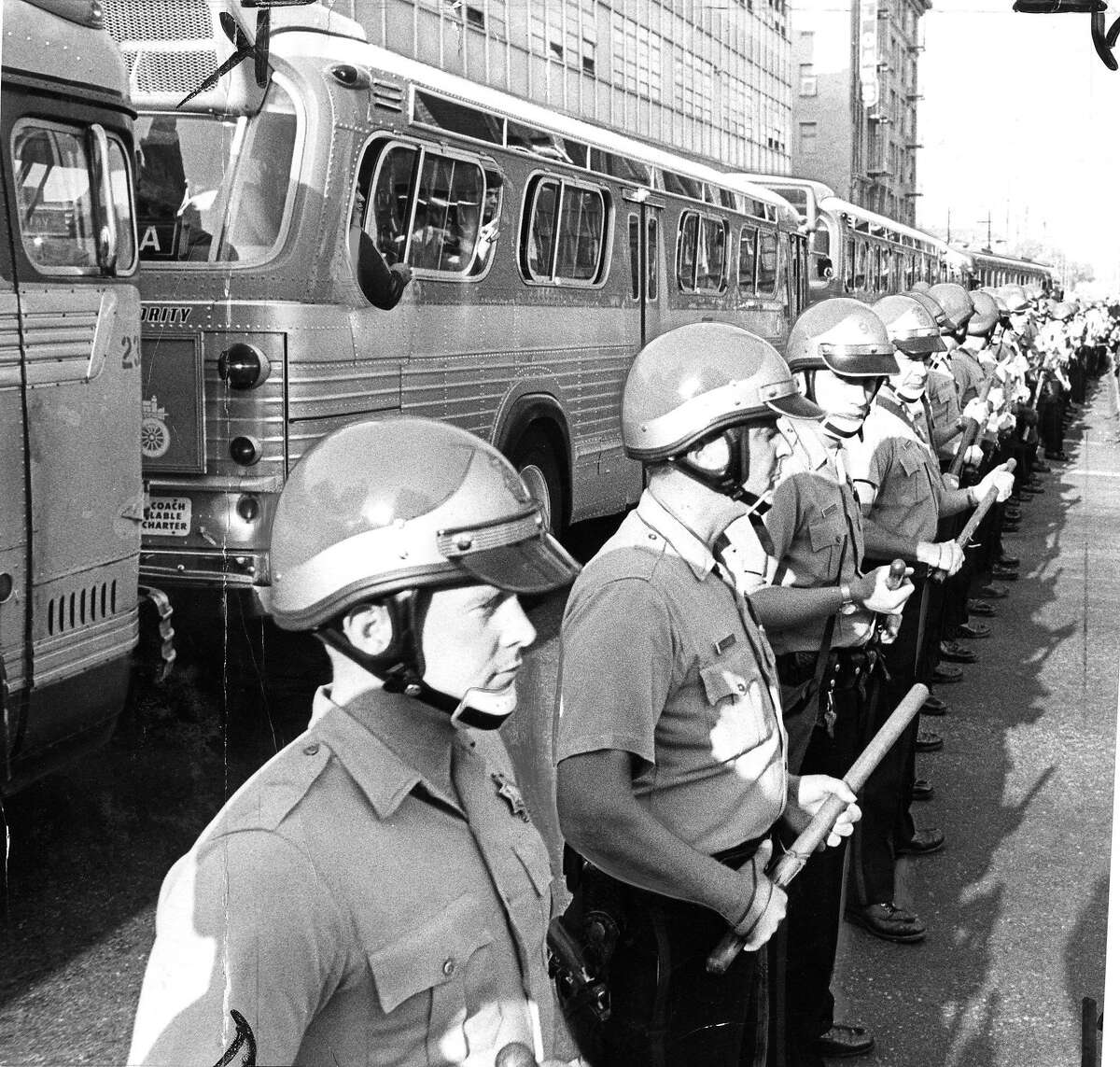 Police are escorting buses of inductees through anti-war demonstrators who are blocking access to the Oakland Induction Center, October 16, 1967 Draft and Vietnam War protesters Phot ran 10/17/1967, p. 1