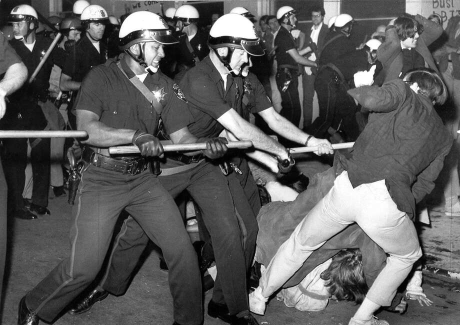 Police use clubs and Mace to move anti-war demonstrators blocking access to the Oakland Induction Center on Oct. 17, 1967.