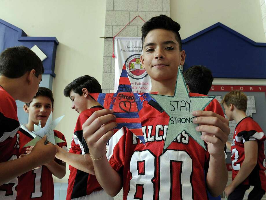 "Mateus Pesarini, 13, a football player at the New Fairfield Middle School, shows his support for victims of Hurricane harvey in Texas, Friday, Sept. 15, 2017. Each New Fairfield school has adopted a ""sister school"" in Houston that they will raise money for to help with the Hurricane Harvey relief. New Fairfield Middle School has asked students to dress in red, white and blue Friday, Sept. 15, 2017.  (Texas and American colors) and each bring in at least $1 to donate to the sister school. Photo: Carol Kaliff / Hearst Connecticut Media / The News-Times"