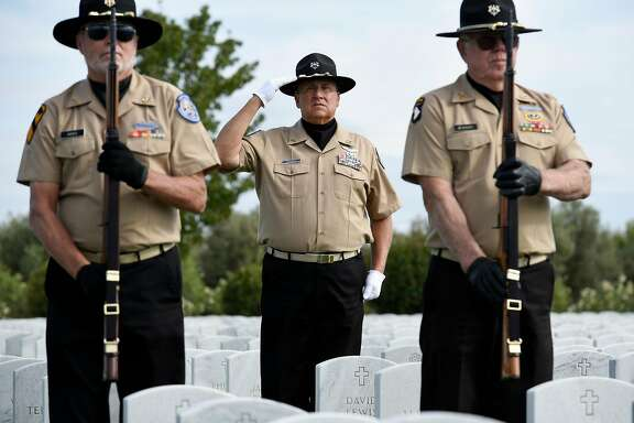 Sacramento Valley National Cemetery Honor Guard member Lu Pietrowski, center, salutes as Jerry Hicks, left, and Tom Murry stand at attention during a funeral honors demonstration at the Sacramento Valley National Cemetery in Dixon, Calif., on Thursday September 14, 2017.
