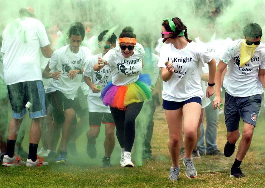 Becca Ferrante, an 11th-grader at Stamford High School wears a rainbow skirt as she and other students, teachers and administrators emerge from a cloud of chalk dust during the first annual U-Knight color run/walk at Stamford High School on Friday, Sept. 15, 2017 in Stamford, Connecticut. The event help bring the high school community together with 175 participating to raise over $5000 dollars to help fund classroom projects, an After Prom Party sponsored by the PTO and after school programs not funded by the school district.