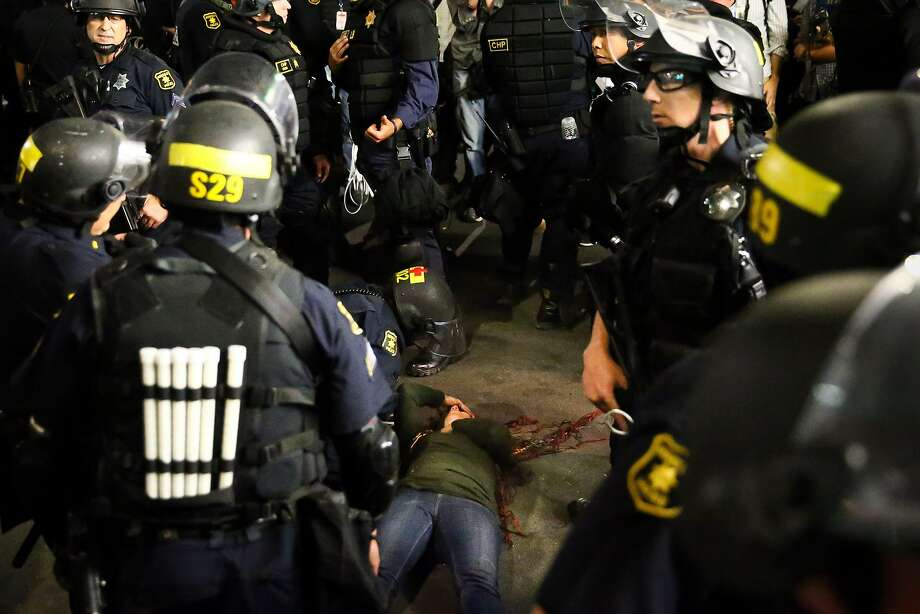 Police officers surround a supporter of conservative Ben Shapiro after she was knocked down during a scuffle with protesters. following a speech by Shapiro, September 14, 2017 at the University of California, Berkeley. / AFP PHOTO / Elijah NouvelageELIJAH NOUVELAGE/AFP/Getty Images Photo: ELIJAH NOUVELAGE, AFP/Getty Images