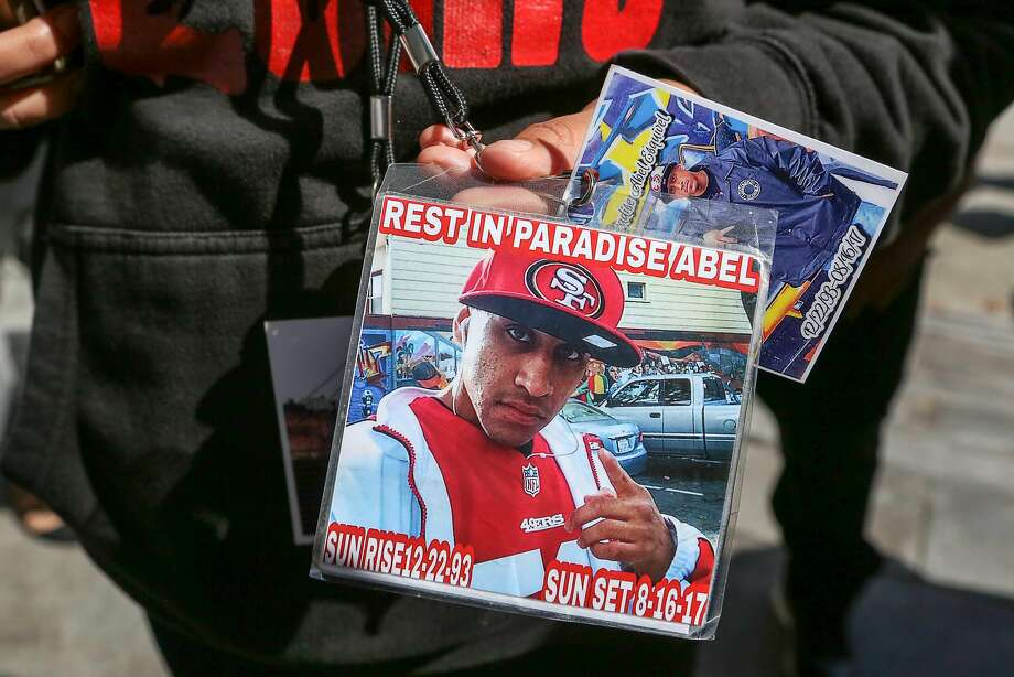 The girlfriend of Abel Enrique Esquivel (who did not wish to be identified) holds up several badges dedicated to Abel that she wears around her neck after the arraignment of the man accused of murdering him on Thursday, September 14, 2017 at the Hall of Justice in San Francisco, Calif. Photo: Amy Osborne, Special To The Chronicle