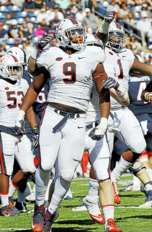 Virginia's Andrew Brown (9) and Donte Wilkins (1) celebrate a sack of UConn quarterback Bryant Shirreffs last season. Photo: The Associated Press File Photo / Copyright 2016 The Associated Press. All rights reserved.