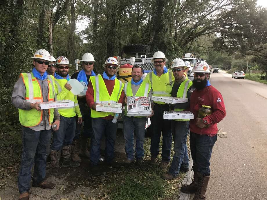 Several Xcel Energy linemen from across the Texas South Plains districts hold gifts of pizza that Tampa, Florida-area residents gave them. One is also holding a jar of pickles that was a gift from an appreciative customer. Shown are Dustin Bach of Plainview (left), Oscar Oscornio of Levelland, Logan Gardner of Plainview, OJ Zapata of Littlefield, Tory Blackwell of Levelland, Terry Smith of Littlefield, Brandon Zahn of Plainview and Isaiah Flores of Levelland. Behind Bach and Oscornio is an unidentified contractor.