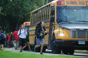 Norwalk High School students catch their First Student buses after school Friday, Sept. 15, in Norwalk. Nearly two weeks into the school year, Norwalk Public Schools are still struggling with bus routes, some of which have been consolidated.