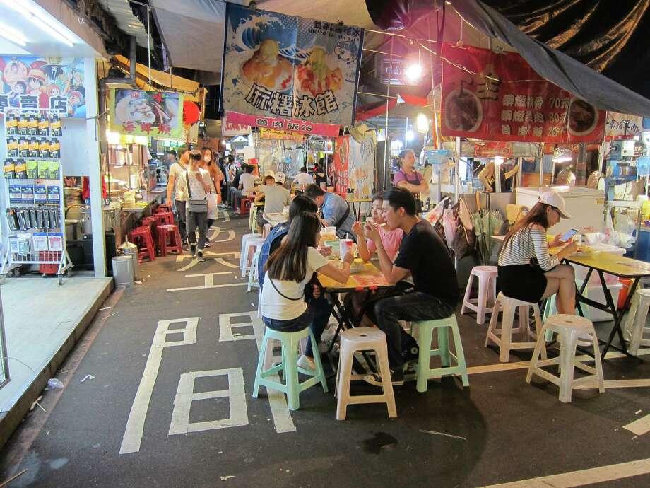 Young Taiwanese feast on street food at Raohe Night Market in Taipei. Photo: Mai Pham
