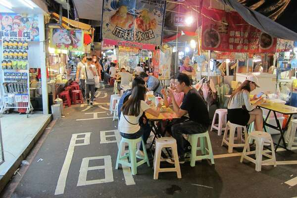 Young Taiwanese feast on street food at Raohe Night Market in Taipei.