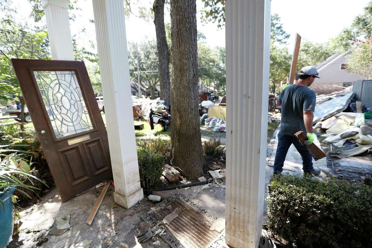 Workers clean out a flood-gutted home in the Memorial Glen subdivision in Houston.