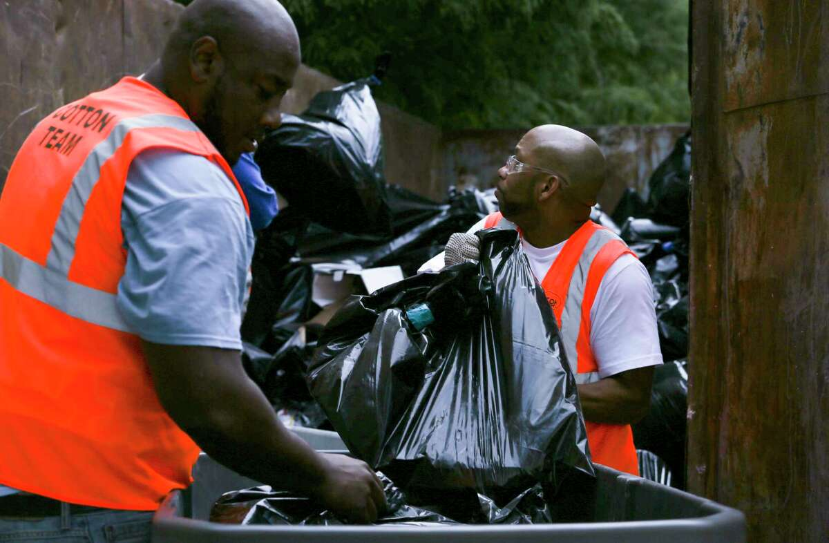 Contractors Brent Brooks, left, and Jermaine Green move bags of sheetrock and carpet torn from Harris County Juvenile District Courts building, which was damaged by Tropical Storm Harvey, into a trailer dumpster Tuesday, Sept. 5, 2017, in Houston. Several Harris County district courthouses are damaged due to water problems caused by Harvey. ( Yi-Chin Lee / Houston Chronicle )