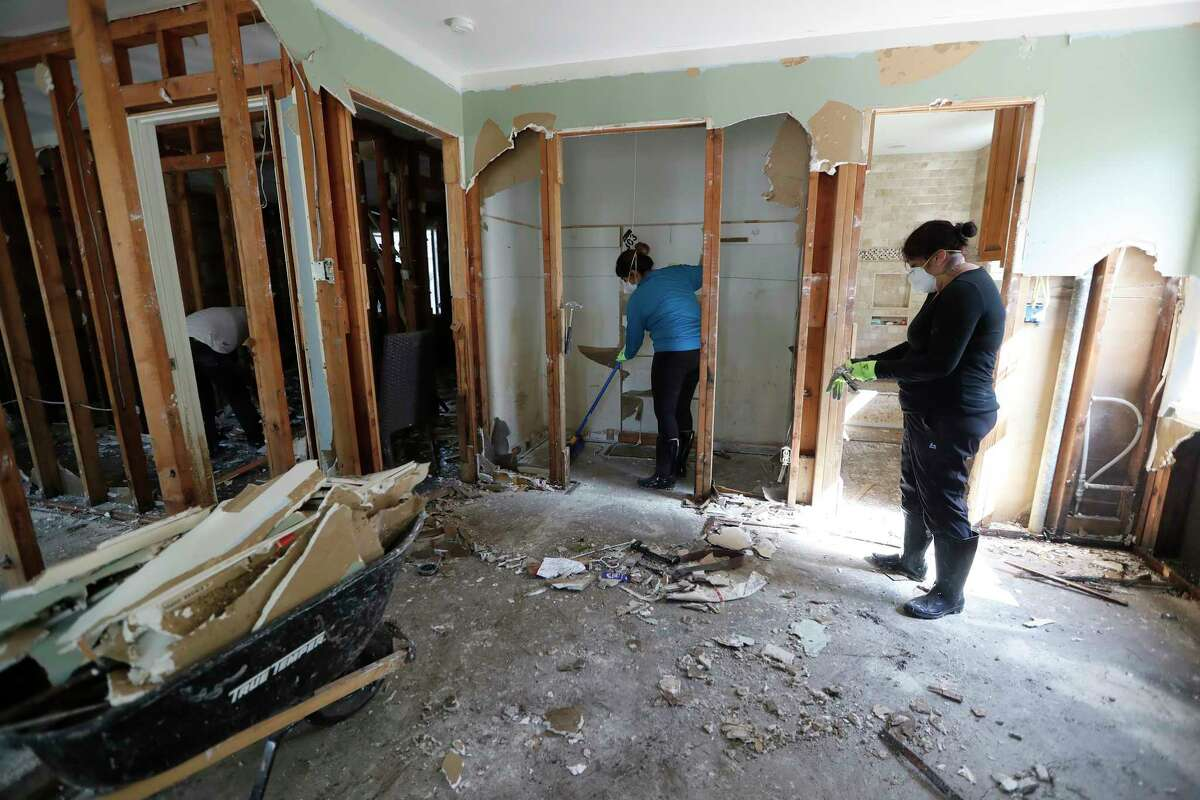 Workers clean out the Otermat's flood gutted home in the Memorial area Sept. 8. Hundreds of homes in the area were flooded after releases from west Houston reservoirs. ( Karen Warren / Houston Chronicle )