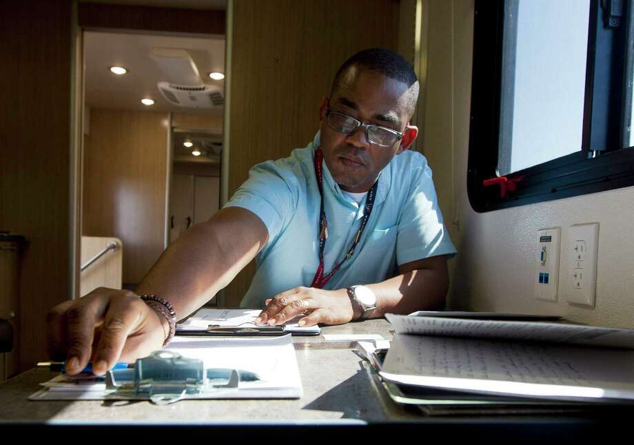Veterans Outreach Program Specialist Marcus Smith goes through paperwork on Sept. 7 after visiting with a veteran at the Veterans Affairs' Mobile Vet Center in Porter. The mobile center is one of six such service centers in Houston. Photo: Jason Fochtman, Staff Photographer / © 2017 Houston Chronicle