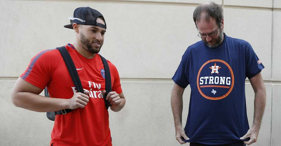 """Houston Astros George Springer waits while Chris Tucker, a truck driver from New Britain, Conneticut, puts on a """"Houston Strong Astro t-shirt. Tucker delivered a truck load of donations collected by Springer and his family for Harvey relief, before the start of an MLB baseball game at Minute Maid Park, Friday, Sept. 15, 2017, in Houston.  ( Karen Warren / Houston Chronicle ) Photo: Karen Warren/Houston Chronicle"""