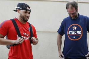 """Houston Astros George Springer waits while Chris Tucker, a truck driver from New Britain, Conneticut, puts on a """"Houston Strong Astro t-shirt. Tucker delivered a truck load of donations collected by Springer and his family for Harvey relief, before the start of an MLB baseball game at Minute Maid Park, Friday, Sept. 15, 2017, in Houston.  ( Karen Warren / Houston Chronicle )"""