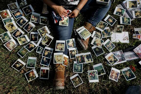 Rikki Saldivar goes through old family photos at a house that belonged to her grandparents, Belia Rojas Saldivar and Manuel Quintanilla Saldivar, Jr., Tuesday, Sept. 5, 2017, in Houston. The pair and four great-grandchildren drowned in a van in Greens Bayou during Tropical Storm Harvey.  ( Jon Shapley  / Houston Chronicle )