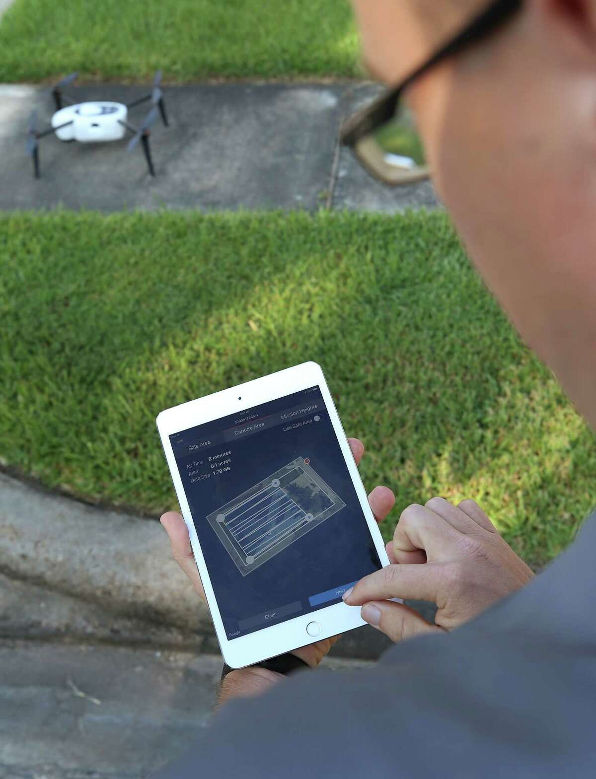 Brent Hazen, Farmers Insurance property claim representative, uses an iPad to set up the perimeter for a drone to examine the damages of a policy holder on the 4500 block of Ambrosia Springs Lane Tuesday, Sept. 12, 2017, in Katy, Texas. ( Godofredo A. Vasquez / Houston Chronicle )