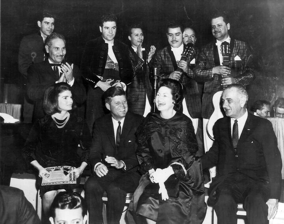 Fernando Herrera stands directly behind President John F. Kennedy in a ballroom at the Rice Hotel in Houston on Nov. 21, 1963. Herrera and guitarist George Gamez (top left) performed at a LULAC dinner honoring the president the night before he was assassinated in Dallas. Photo: Courtesy Fernando Herrera