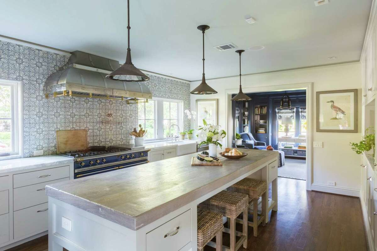 The kitchen in the River Oaks home of restaurateur Tracy Vaught and chef Hugo Ortega has luxurious wall tile and a custom range hood as focal points.