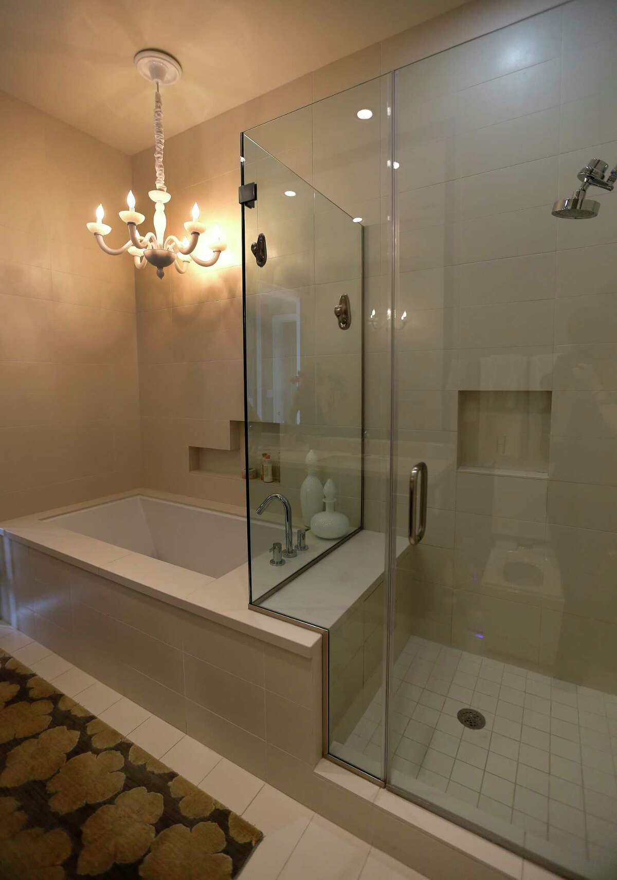 The master bathroom with a chandelier over the tub at the home of Doctors Kathy Frazar and Tom Hedge at Highland Tower,Thursday, April 28, 2016, in Houston. The couple moved from a West U home to an inner loop high rise after their daughter left for college. The empty nesters wanted a home with a more modern aesthetic to streamline their busy lifestyle. They've hired an interior designer, Cheryl Baker, and did a substantial remodeling job throughout. ( Karen Warren / Houston Chronicle )