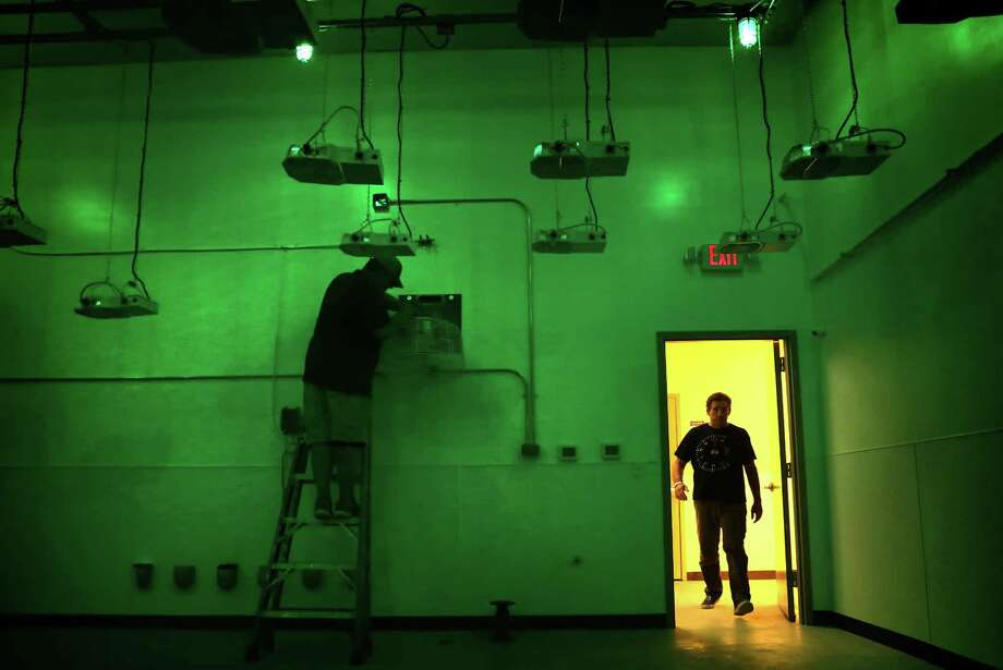 Morris Denton, CEO of Compassionate Cultivation, walks into a vegetative room lit with green lights which simulates night time for marijuana plants that will be grown in the room, where a climate control person is working.   Denton is one of only three entities expected to soon get a license to grow medical cannabis, in his soon to open location in South Austin. Photo: Bob Owen, Staff / San Antonio Express-News / ©2017 San Antonio Express-News