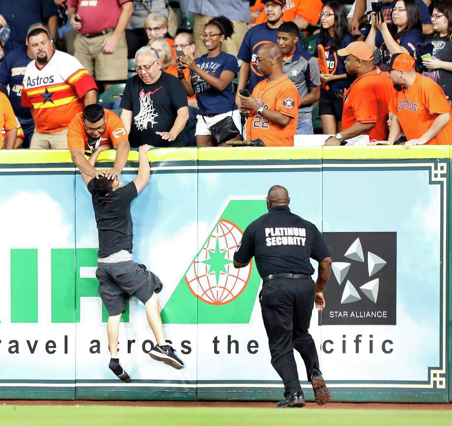 PHOTOS: A look at the fan who ran onto the fieldA security officer in the stands tries to push a man back on the field so that police could catch him as he ran out onto the field during the first inning of an MLB baseball game at Minute Maid Park, Friday, Sept. 15, 2017, in Houston.Browse for more photos of the epic chase. Photo: Karen Warren, Houston Chronicle / @ 2017 Houston Chronicle