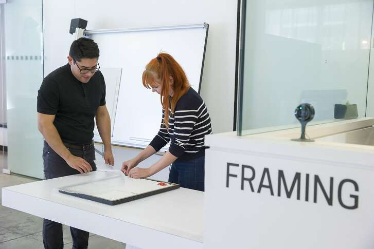 From left: Director of operations Carlos Arrieta and production manager Kristen Wrzesniewski carefully wrap Katie Hughes' new framed photo at Neomodern on Saturday, Sept. 9, 2017, in San Francisco, Calif.