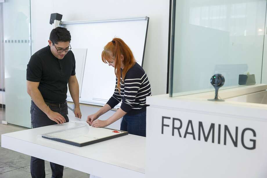 Director of operations Carlos Arrieta and production manager Kristen Wrzesniewski carefully wrap Katie Hughes' new framed photo at Neomodern. Photo: Santiago Mejia, The Chronicle