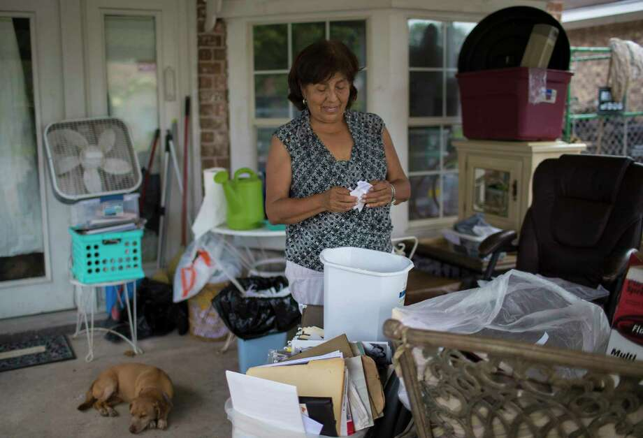 Longtime South Houston resident Irene Tamayo, above, goes over Hurricane Harvey-damaged documents and old photographs in September. Three months after Harvey, poor and minority communities are still struggling to rebuild from a storm that disproportionately affected them, and which worsened chronic issues related to inequality, according to a report released last week by the Kaiser Family Foundation and the Episcopal Health Foundation. Photo: Marie D. De Jesus, Staff / © 2017 Houston Chronicle