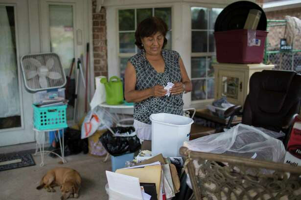 Longtime South Houston resident Irene Tamayo, above, goes over documents and old photographs damaged by the floods caused by Hurricane Harvey. Below, Raul Mendez, 67, is among the residents in South Houston waiting for FEMA officials to inspect their homes and provide support. .
