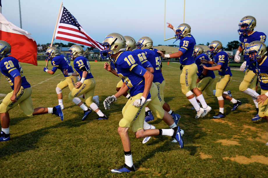 Hamshire-Fannett players run onto the field before the Rice Bowl rivalry football between Hamshire-Fannett and East Chambers. The two communities were both severely flooded by Tropical Storm Harvey.  Photo taken Friday 9/15/17 Ryan Pelham/The Enterprise Photo: Ryan Pelham / ©2017 The Beaumont Enterprise/Ryan Pelham