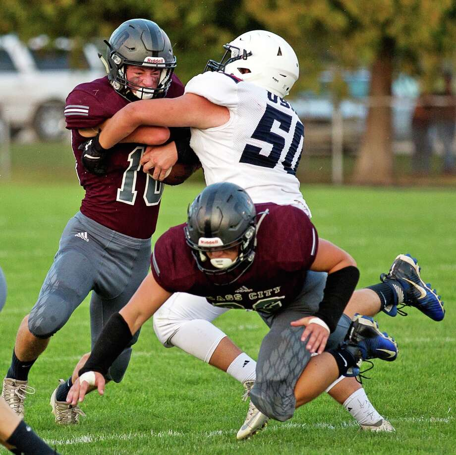 p.p1 {margin: 0.0px 0.0px 0.0px 0.0px; line-height: 10.8px; font: 10.0px Helvetica}Cass City running back Brendan Hamilton (10) attempts to break through the tackle of USA's Myles Geiger (50) during the first half of the Red Hawks' 18-14 win, Friday night, in Cass City. (Kaitlin's Klicks/For the Tribune)