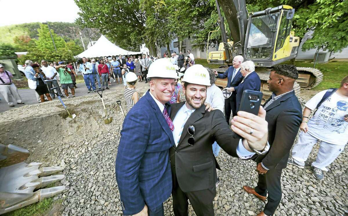Michael Storz, left, president of Chapel Haven, and consultant Nathan Gregoire of CCS Fundraising take a selfie together after a ground-breaking celebration for a multi-year campus expansion Friday in New Haven.